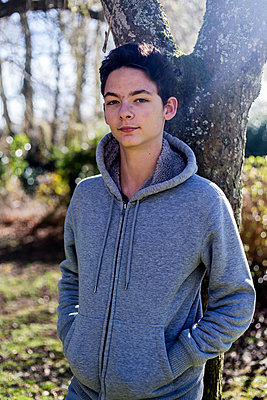 Teenager standing aginst a tree - p940m1132356 by Bénédite Topuz