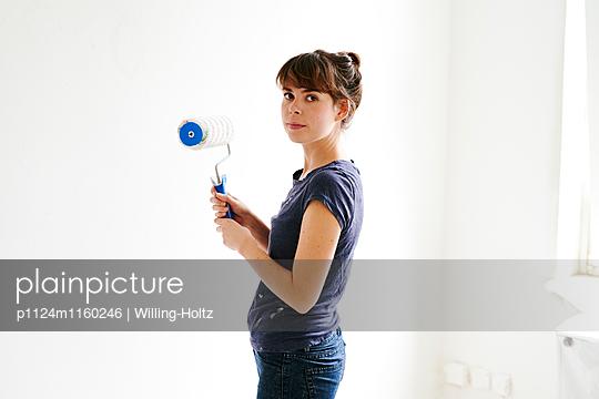 Junge Frau mit Farbrolle - p1124m1160246 von Willing-Holtz