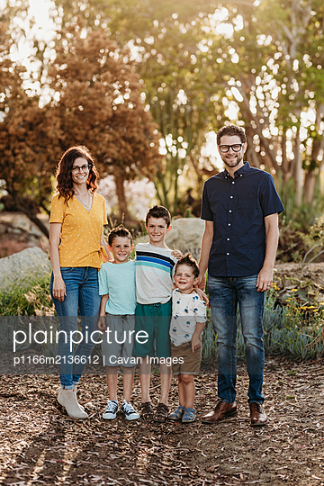 Portrait of family smiling at camera in sunny cactus garden - p1166m2136612 by Cavan Images
