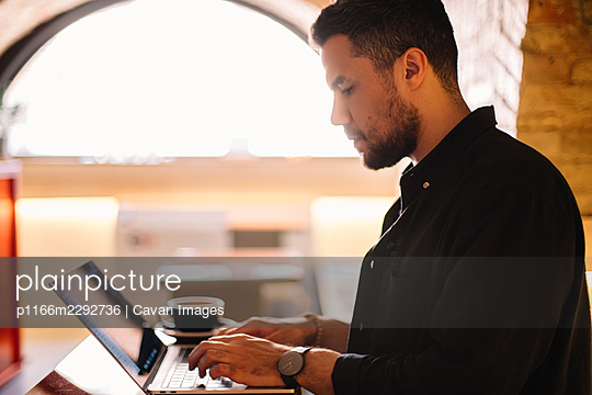 Serious man using laptop computer at cafe - p1166m2292736 by Cavan Images