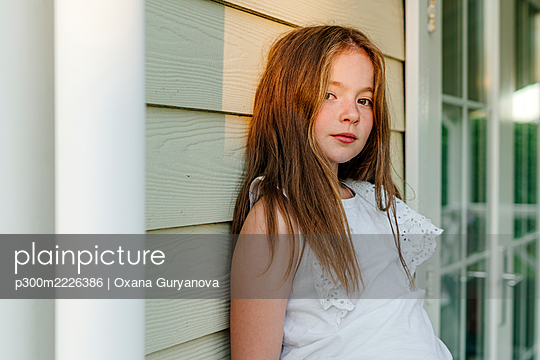 Girl leaning on wall during sunny day - p300m2226386 by Oxana Guryanova