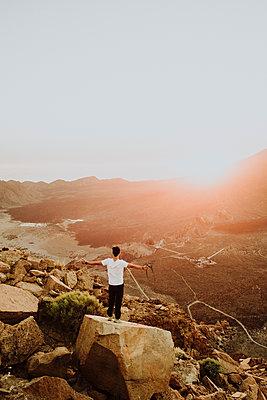 Man standing on rock watching sunset at caldera of Ca̱adas del Teide - p1166m2129913 by Cavan Images