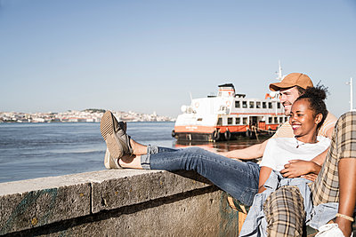 Happy young couple sitting at the waterfront, Lisbon, Portugal - p300m2144906 by Uwe Umstätter