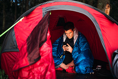 Man camping in Estonia, sitting in his tent, using smartphone - p300m2219369 by Kike Arnaiz