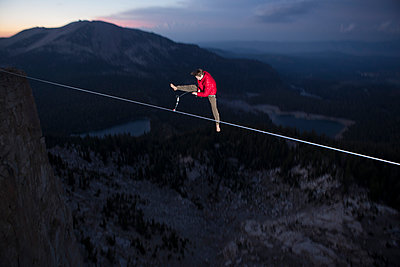 Male highliner jumps off a 125 foot highline over lakes in a gap on top of Mammoth Crest  - p343m1003005f by Jared Alden