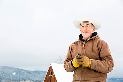 Caucasian farmer smiling in snow - p555m1312057 by Inti St Clair