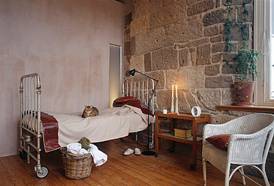 Guest bedroom with reclaimed hospital bed and cat and exposed stone wall - p8551959 by David Churchill