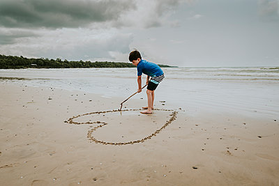 Boy making heart shape on sand at beach against cloudy sky - p1166m2034670 by Cavan Images