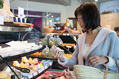 Senior woman browsing deli display in grocery store - p1192m1567212 by Hero Images