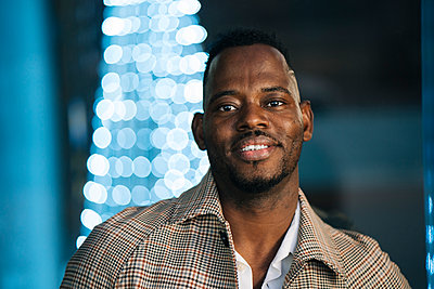 Smiling African man in coat at night - p300m2256937 by Manu Padilla Photo