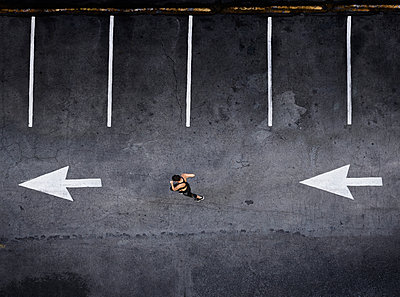 Aerial view of Pacific Islander woman running in parking lot - p555m1219404 by Colin Anderson