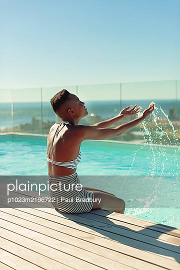 Carefree young woman splashing water at sunny swimming pool - p1023m2196722 by Paul Bradbury