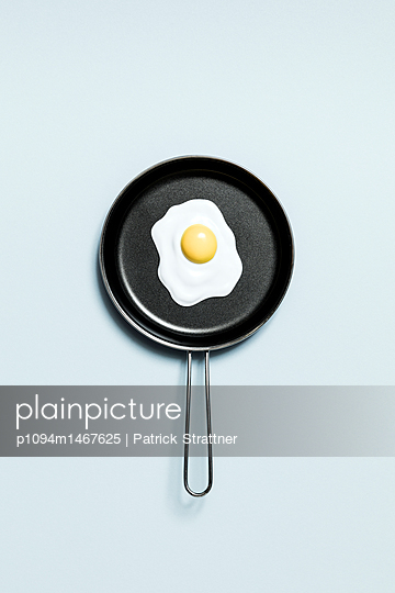 Directly above view of fried egg in toy cooking pan on blue background - p1094m1467625 by Patrick Strattner