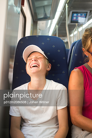 Boy laughing on train - p312m2086508 by Johan Willner
