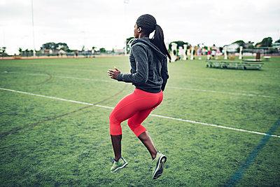 Full length of determined female athlete exercising on field - p1166m1086162f by John Trice