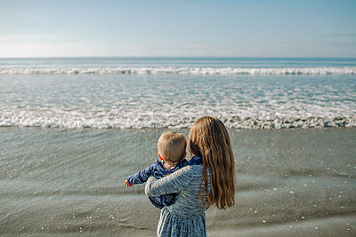 Rear view of girl carrying sister at beach - p1166m1513018 by Cavan Images