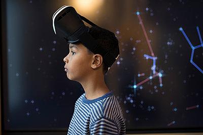 Pensive boy wearing virtual reality simulator glasses looking away - p1192m1194243 by Hero Images
