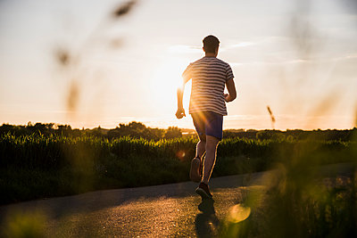 Germany, young man jogging, against the sun - p300m1153503 by Uwe Umstätter