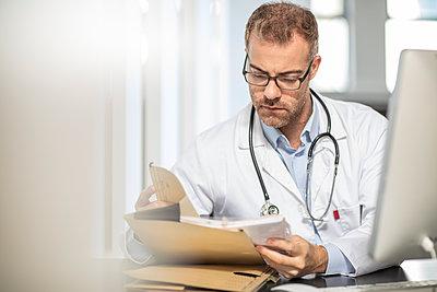 Doctor working at desk in medical practice - p300m2005266 von zerocreatives