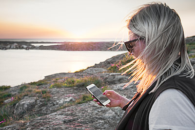Woman using cell phone at sea - p312m2207634 by Viktor Holm
