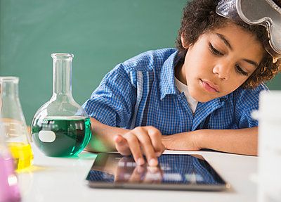 Mixed race boy using digital tablet in classroom science lab - p555m1421112 by JGI/Jamie Grill
