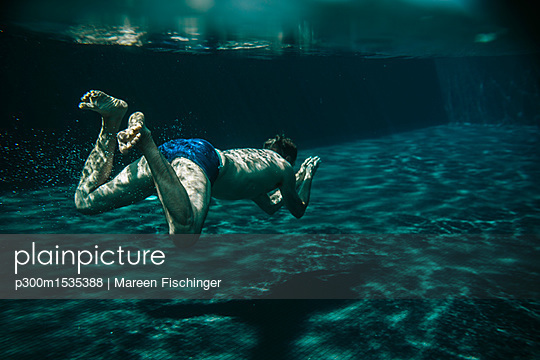 Man diving in a swimming pool - p300m1535388 by Mareen Fischinger