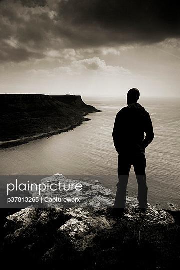 Man standing on cliff - p37813265 by Captureworx