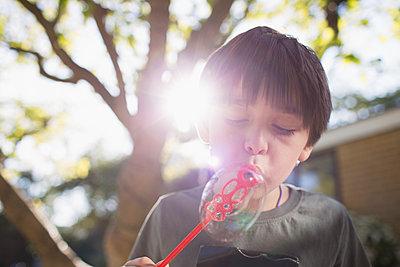 Boy blowing bubbles in sunny backyard - p1023m2208288 by Tom Merton