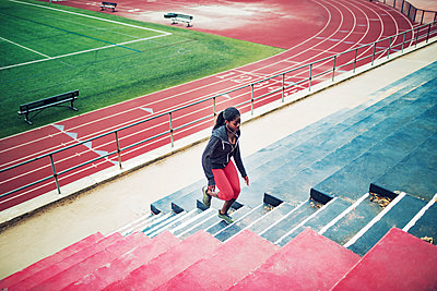 High angle view of sportswoman running on steps at stadium - p1166m1086166f by John Trice