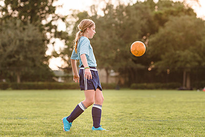 Side view of girl playing soccer at field - p1166m1541891 by Cavan Social