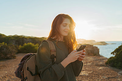 Redheaded young woman using cell phone at the coast at sunset, Ibiza, Spain - p300m2159909 by VITTA GALLERY