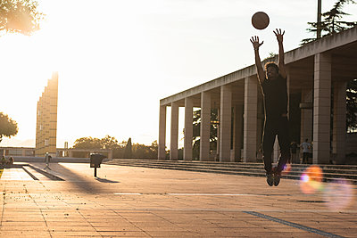 Young man playing basketball on footpath against clear sky at sunset - p300m2243332 by NOVELLIMAGE