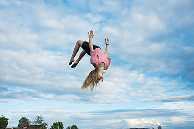 Girl doing somersault mid-air - p312m1114080f by Johan Willner