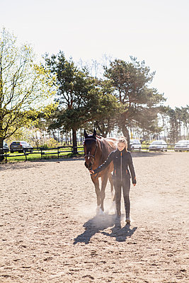 Teenage girl leading a horse in Sweden - p352m2040624 by Serny Pernebjer