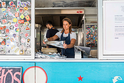 Confident young female owner holding foil against colleague working in food truck - p426m2046506 by Maskot