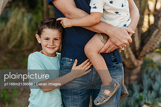 Mid view of elementary age boy hugging father and brother and smiling - p1166m2136666 by Cavan Images