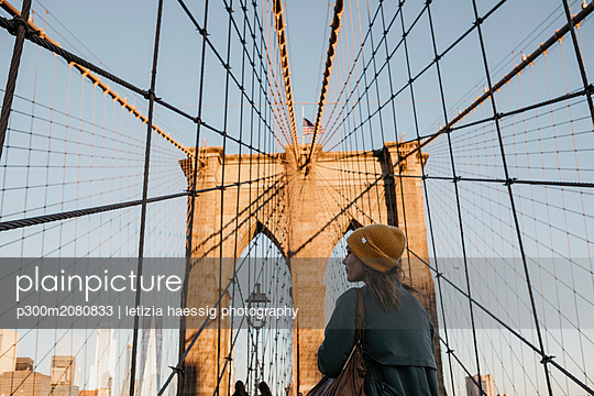 USA, New York, New York City, female tourist on Brooklyn Bridge in the morning light - p300m2080833 by letizia haessig photography