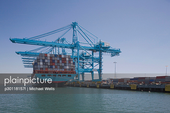 Container ship below cranes at a commercial dock - p30118157f by Michael Wells