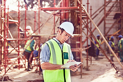 Construction worker using digital tablet at construction site - p1023m1402902 by Trevor Adeline