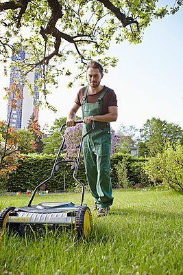 Young man mowing lawn with push mower - p300m818812f by Rainer Holz