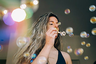 Young woman blowing bubbles - p301m2213598 by Alexandra C. Ribeiro