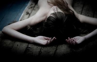 Woman lying on a wooden floor - p8430037 by Rea Stein