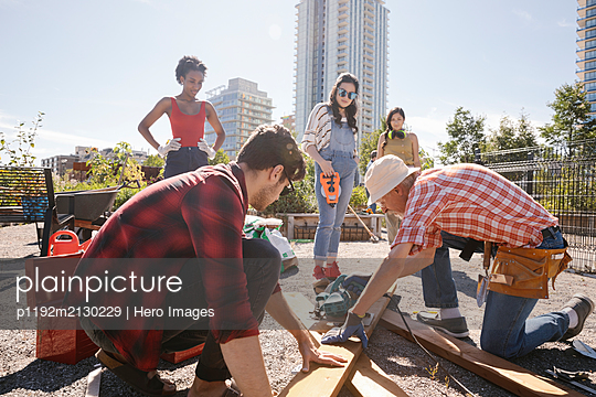 Man guiding young adults building planter box in sunny community garden - p1192m2130229 by Hero Images