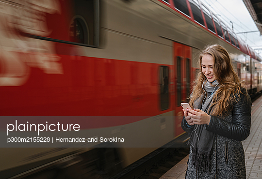 Smiling young woman standing on platform using smartphone and earphones, Vilnius, Lithuania - p300m2155228 by Hernandez and Sorokina