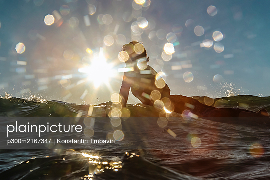Female surfer on surfboard against the sun, Bali, Indonesia - p300m2167347 by Konstantin Trubavin