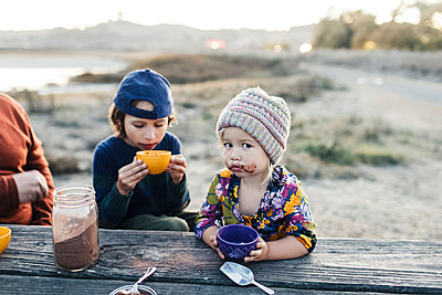 Adorable girl with brother drinking hot cocoa by woodden table at twilights - p1166m2095156 by Cavan Images
