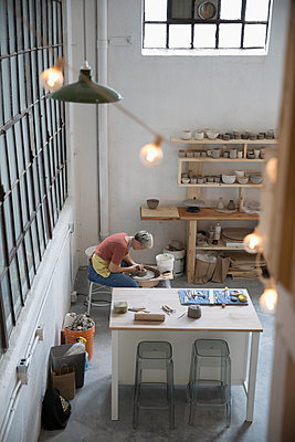 Elevated view female pottery using pottery wheel in art studio - p1192m1490251 by Hero Images