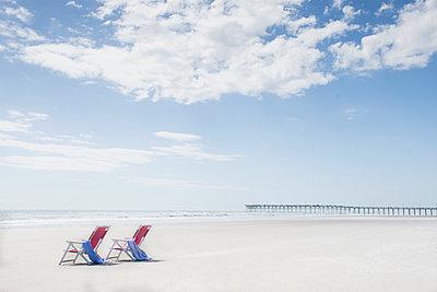 Deck chairs on sandy beach by Atlantic Ocean - p1427m1553594 by Chris  Hackett