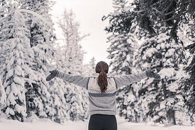 Junge Frau im Winter streckt die Arme in die Luft  - p1455m1574495 von Ingmar Wein