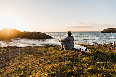 France, Bretagne, Crozon peninsula, woman sitting at the coast at sunset with surfboard - p300m1189291 by Uwe Umstätter